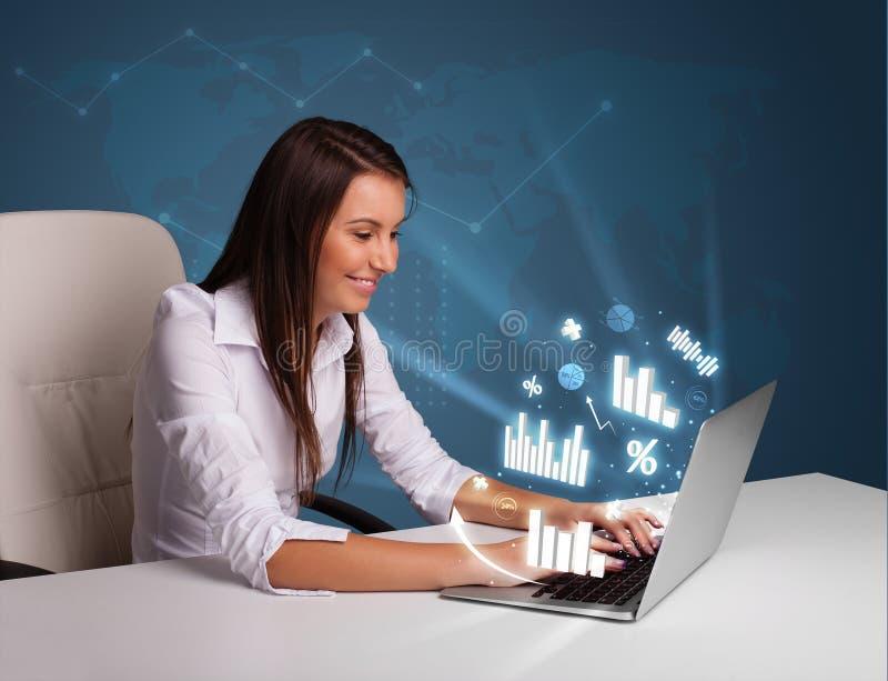 Nätt kvinnasammanträde på skrivbordet och maskinskrivning på bärbara datorn med diagram arkivbilder