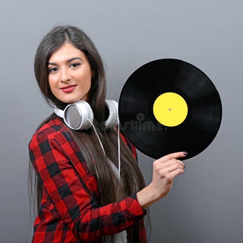 Nätt kvinnlig discjockey med hörlurar och vinyl mot grå bakgrund royaltyfri foto