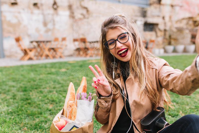 Nätt kvinnlig fotograf som gör selfie som sitter på gräset med bageripåsen och visar att le för fredtecken _ arkivfoto
