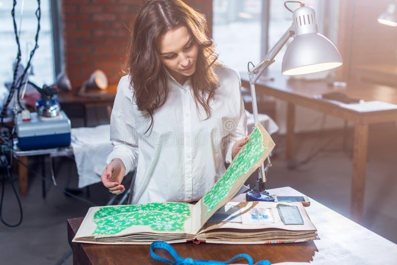 Nätt kvinnlig skräddare som väljer ett tyg i torkdukekatalog i studio arkivbild