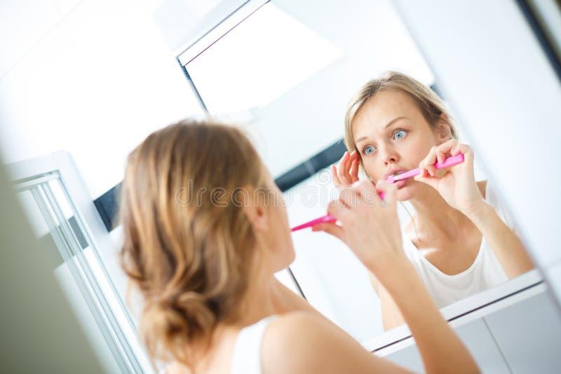 Nätt kvinnlig som framme borstar hennes tänder av spegeln royaltyfria foton