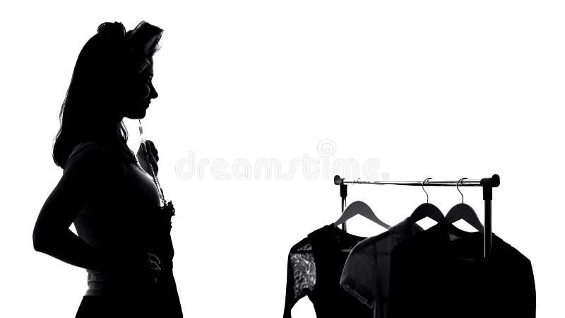 Nätt kvinnlig som väljer klänningen och ser i spegeln som förbereder sig för möte arkivfoto