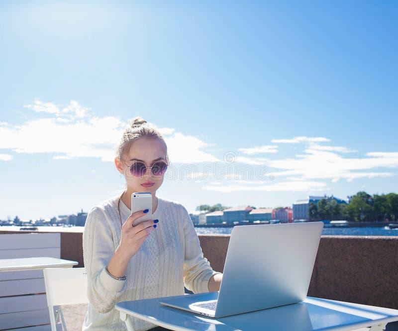 Nätt kvinnlig student som använder celltelefonen och den bärbara netto-boken som vilar nära invallningfloden royaltyfria bilder