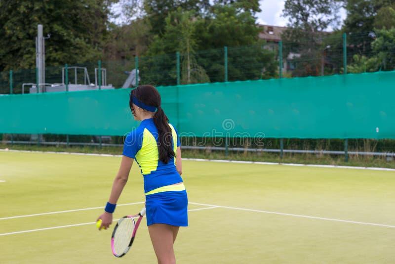 Nätt kvinnlig tennisspelare som bär en sportswear som värmer befo upp arkivfoto