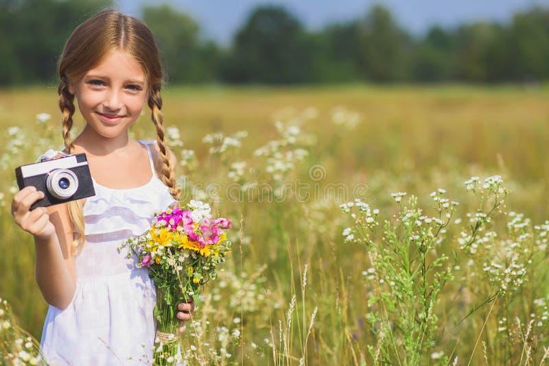 Nätt kvinnligt barn som tar foto på fält royaltyfria foton