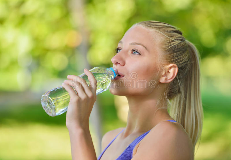 Nätt kvinnligt löparevila och dricksvatten från en flaska, når att ha utarbetat arkivfoton