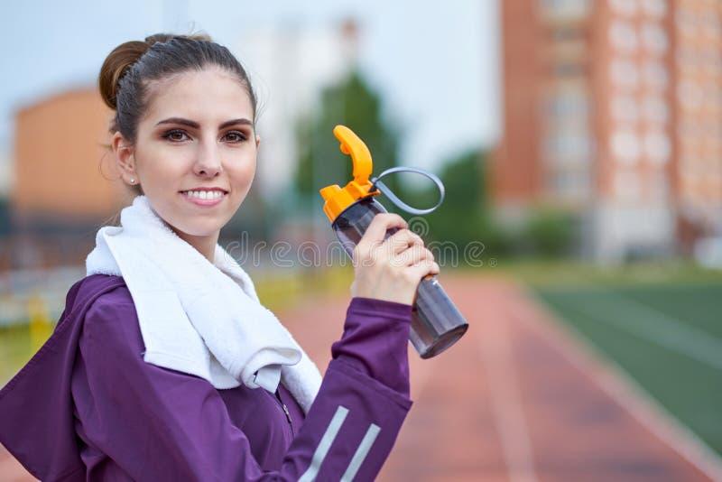 Nätt kvinnligt löparevila och dricksvatten från en flaska, når att ha utarbetat spårkörning av stadion arkivfoton