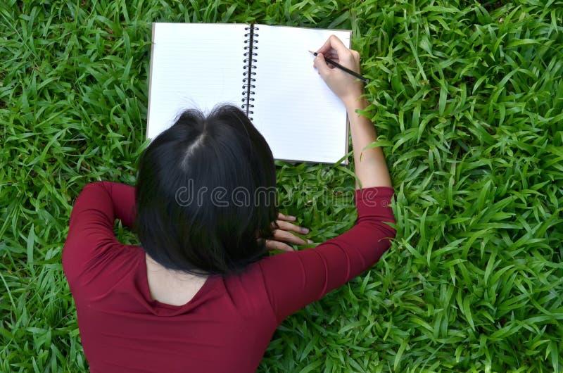 Nätt kvinnor som skriver boken royaltyfri bild