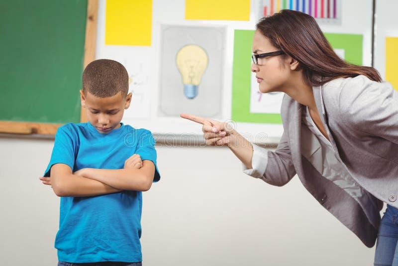Nätt lärare som ger reprimand en elev royaltyfri fotografi