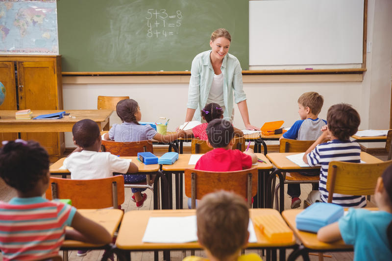 Nätt lärare som talar till de unga eleverna i klassrum arkivfoto