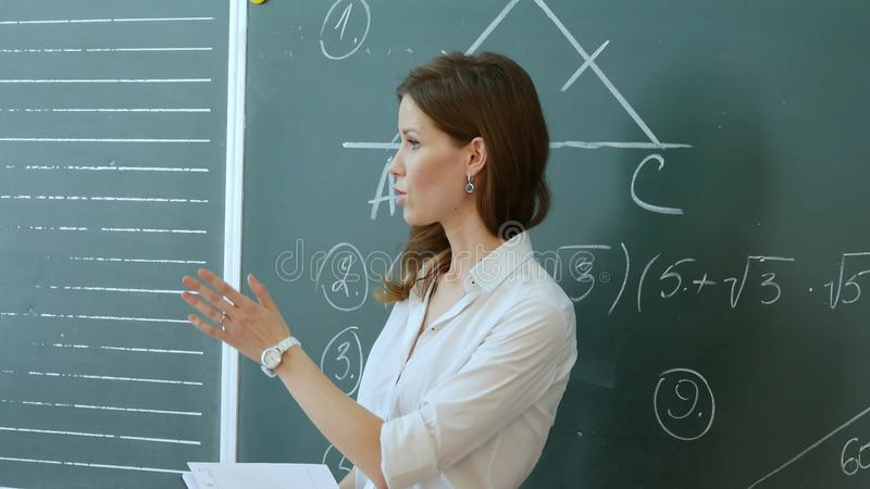 Nätt lärare som talar till eleverna i klassrum royaltyfria bilder