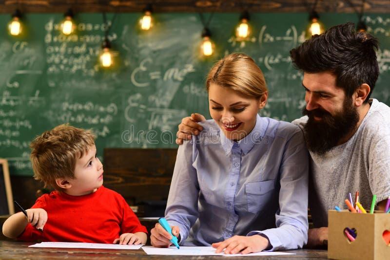 Nätt lärareportionelev i klassrumet på grundskolan, utbildningsaktiviteter i klassrum på den lyckliga skolan arkivfoton