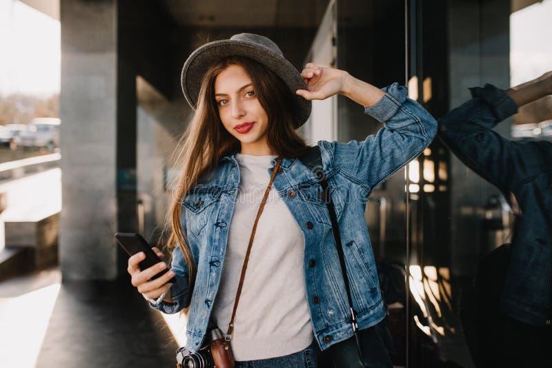 Nätt långhårig flicka i stilfull grov bomullstvilldräkt som utanför går och rymmer väntande på appell för svart smartphone _ arkivbilder