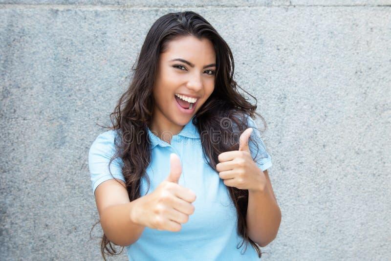Nätt latin - amerikansk kvinna med långt hår som visar båda tummar u royaltyfri fotografi