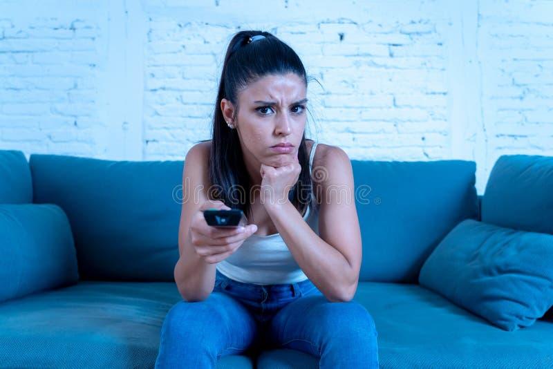 Nätt latinsk kvinna som hemma håller ögonen på en läskig film arkivfoton
