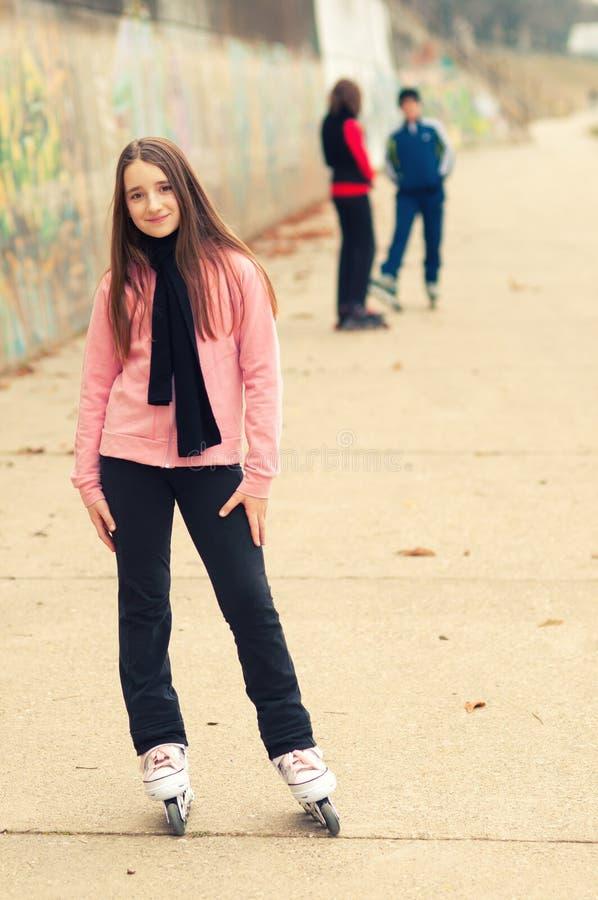 Nätt le flicka på rollerskates som poserar yttersidan med vänner fotografering för bildbyråer