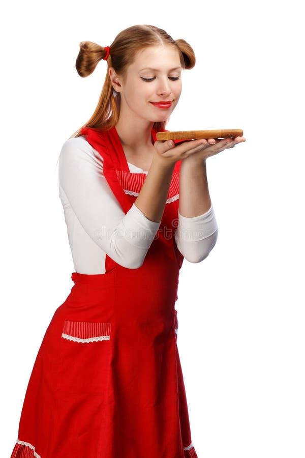 Nätt le hemmafru i rött förkläde med rolig hästsvansholdi royaltyfri foto