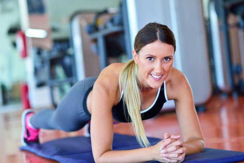 Nätt le konditioninstruktör som gör push-UPS i idrottshallen Ung idrottskvinna som övar på aerobicsgrupp Sjukvård- och viktlo royaltyfri fotografi