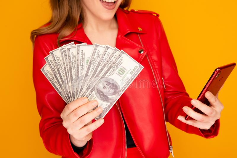 Nätt le kvinna i det röda omslaget som rymmer pengar och telefonen på den gula bakgrunden arkivbilder