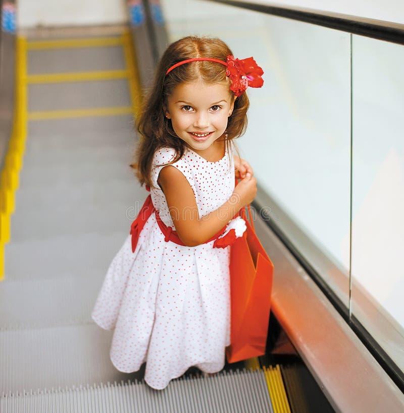 Nätt le liten flicka för stående med shoppingpåsen arkivbilder