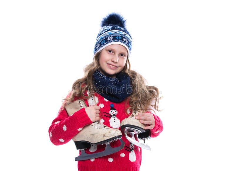 Nätt le liten flicka med den lockiga frisyren som bär den stack tröjan, halsduken och hatten med skridskor som isoleras på vit ba arkivbild
