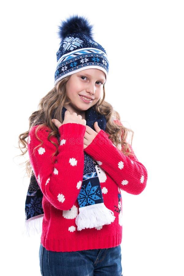Nätt le liten flicka med den lockiga frisyren som bär den stack tröjan, halsduken och hatten med skridskor som isoleras på vit ba fotografering för bildbyråer