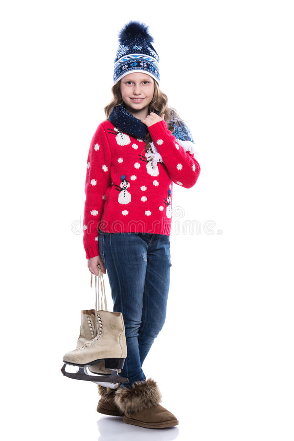 Nätt le liten flicka med den lockiga frisyren som bär den stack tröjan, halsduken och hatten med skridskor som isoleras på vit ba arkivfoton