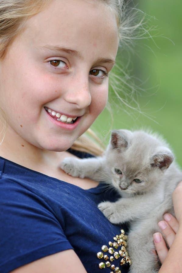 Nätt le lycklig flicka med den nya älsklings- kattungen arkivfoton