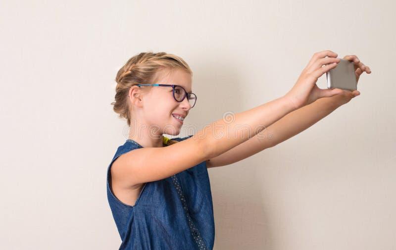 Nätt le tonårig flicka i exponeringsglas som gör selfiefotoet på smart arkivfoto
