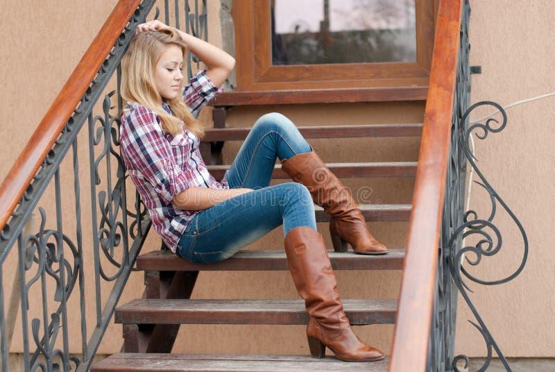 Nätt le tonårs- flickasammanträde på trappan fotografering för bildbyråer