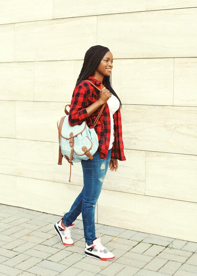 Nätt le ung afrikansk kvinna med att gå för ryggsäck royaltyfri fotografi