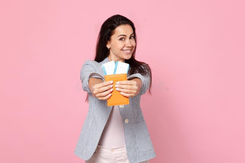 Nätt le ung kvinna i det randiga omslagsinnehavpasset, biljett för logipasserande som isoleras på den rosa pastellfärgade väggen arkivbild