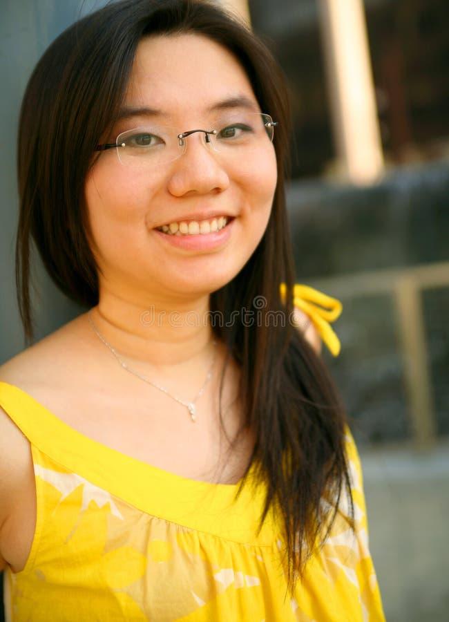 nätt le yellow för asiatisk klänningflicka royaltyfri foto