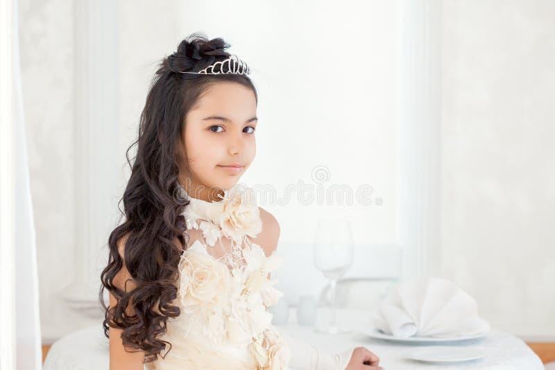 Nätt liten brunett som poserar i tiara, närbild arkivfoton