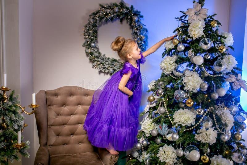 Nätt liten flicka 4 gamla år i en blå klänning Behandla som ett barn i julrum med den teddybear stora klockan, julträdet, brun få royaltyfri fotografi