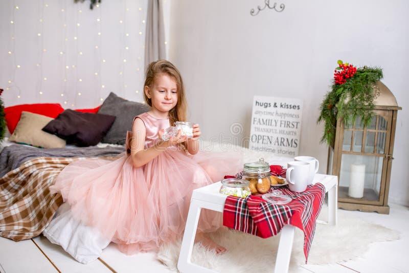 Nätt liten flicka 4 gamla år i en rosa klänning Barn i julrummet med en säng som äter godisen, choklad, kakor och drinken arkivfoto