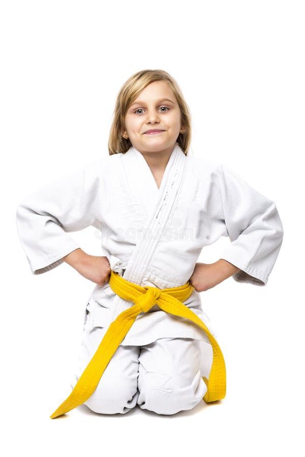 Nätt liten flicka i den vita kimonot ner på knä som är klara att slåss royaltyfria bilder