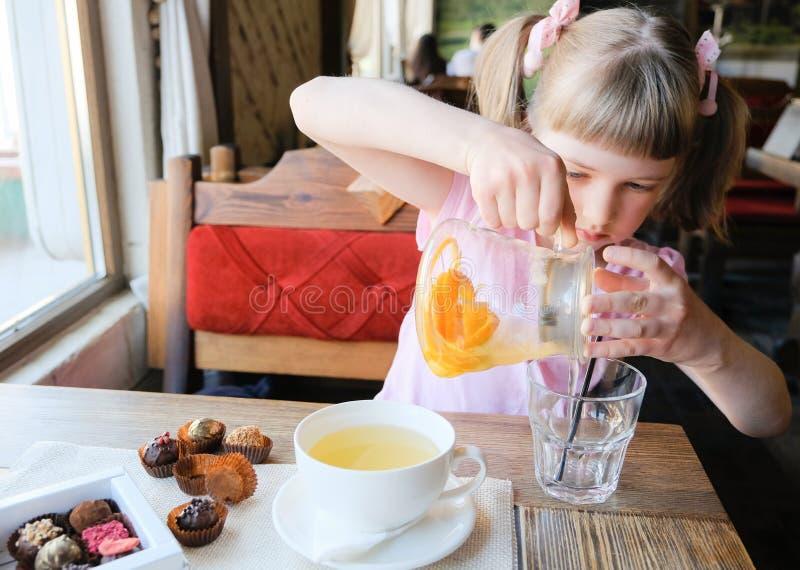 Nätt liten flicka i ett kafé royaltyfri bild