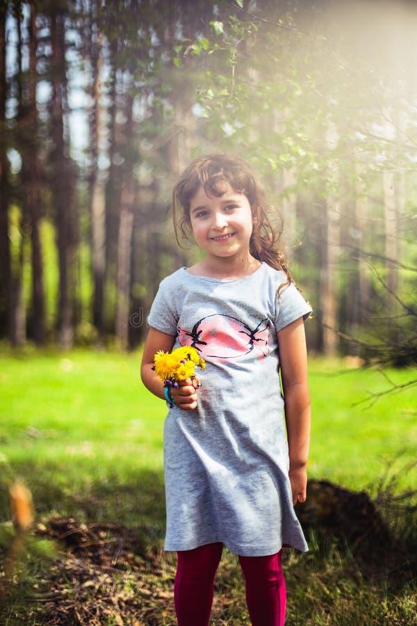 Nätt liten flicka i skogen, vårlandskapbakgrund royaltyfri foto