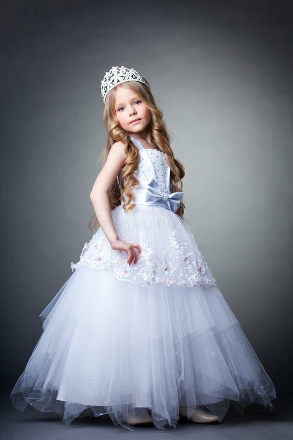 Nätt liten flicka i tiara- och vitklänning royaltyfri bild