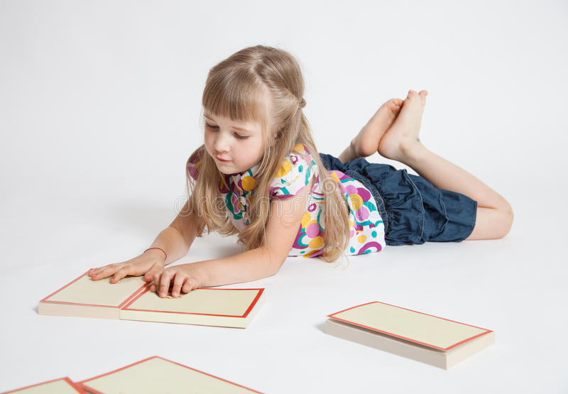 Nätt liten flicka med böcker arkivfoto