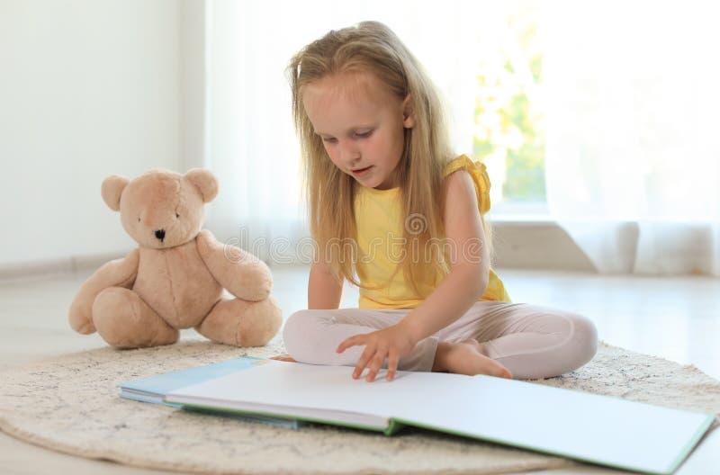 Nätt liten flicka med boken och nallebjörnen på golv royaltyfri fotografi