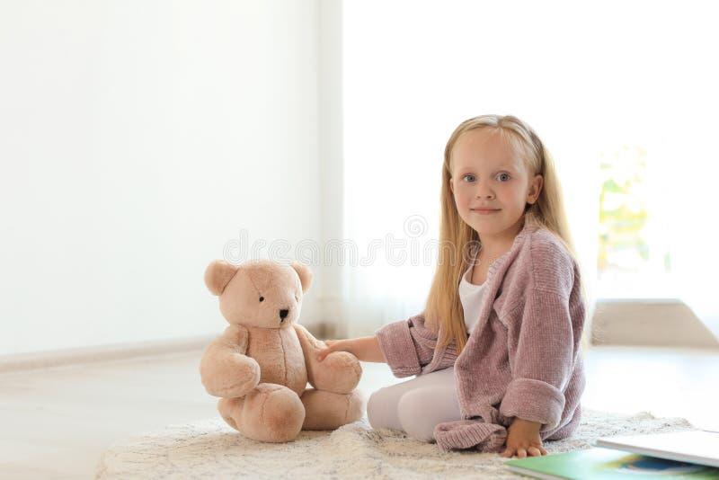 Nätt liten flicka med boken och nallebjörnen på golv royaltyfria foton