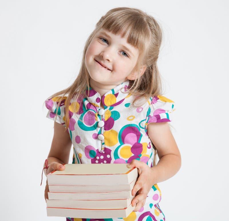 Nätt liten flicka med en bunt av böcker arkivfoton