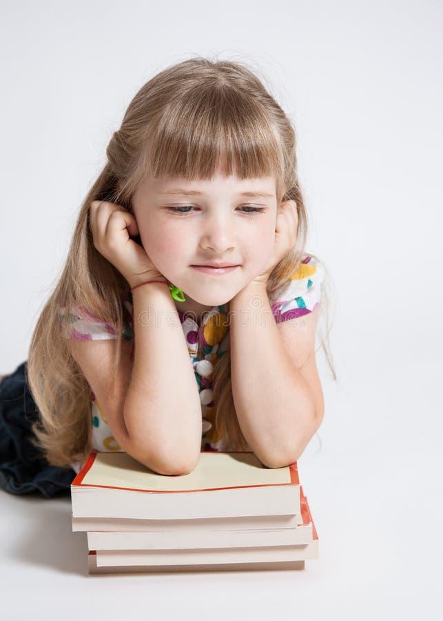 Nätt liten flicka med en bunt av böcker fotografering för bildbyråer
