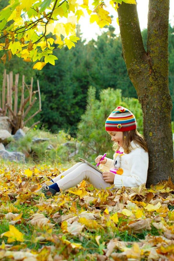 Nätt liten flicka med en minnestavlaPC arkivbild