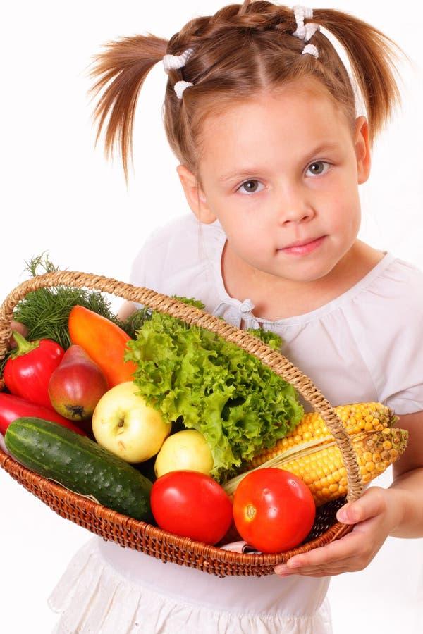Nätt liten flicka med grönsaker och frukter royaltyfri fotografi