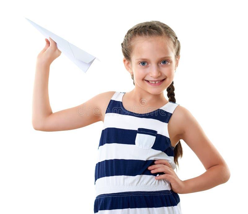 Nätt liten flicka med pappersnivån, randig klänning, studiostående, vit bakgrund royaltyfria foton