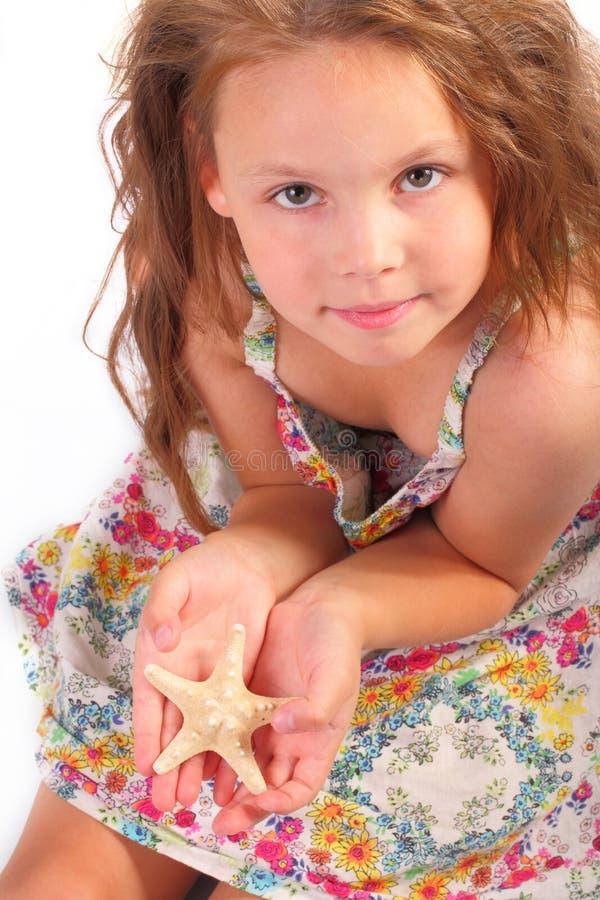 Nätt liten flicka med sjöstjärnan fotografering för bildbyråer