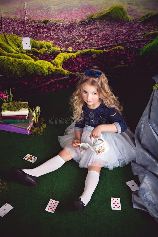 Nätt liten flicka som Alice i hällande te för underland royaltyfri bild